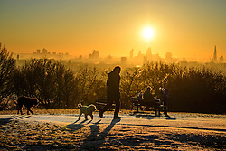 © Licensed to London News Pictures. 29/12/2016. London, UK. A man walks his two dogs on Parliament Hill on Hampstead Heath, London at sunrise, with the city of London in the background. Most of the UK has woken to freezing temperatures. Photo credit: Ben Cawthra/LNP
