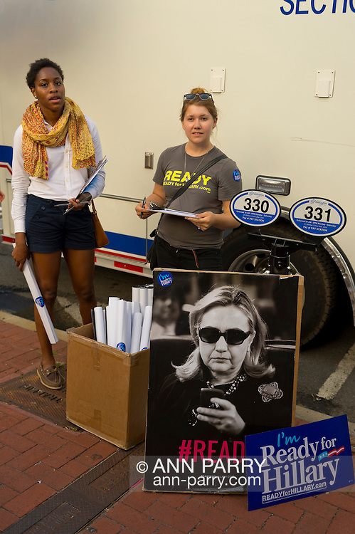 Huntington, New York, U.S. - August 6, 2014 - Two young woman, from the Ready for Hillary super PAC (political action committee), have free Ready for Hillary posters with #READY and Hillary Clinton's photo on them, to hand out outside the front of Book Revue, where Hillary Clinton is having a book signing promoting her new memoir, Hard Choices, in Huntington, Long Island.