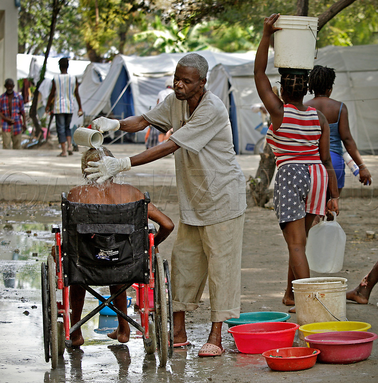 Andree Devilas is bathed by Avenard Joseph Jacquelin outside the Municipal Nursing Home in Port-A-Prince near Delmas 2 on February 27, 2010. The nursing home was destroyed during the earthquake and now the general public has encroached on the nursing home site.
