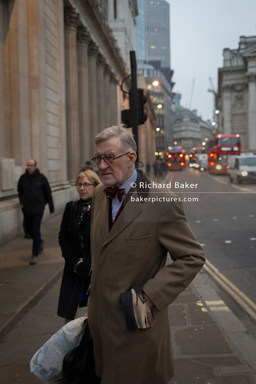 An elderly gentleman wearing a bow tie walks past the Bank of England, on 9th February 2017, in the City of London, England.