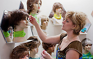 "D Vizecky, of Cedar Rapids, adjusts one of the many displays in the ""wig room"" at Advanced Hair Technologies in Hiawatha on Saturday, May 29, 2010."