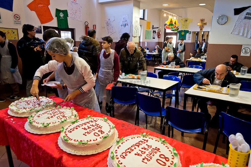 ROME, ITALY  -  DECEMBER 17:   Voluntaries cut the cake offered by Pope Francis to the poor of the Colle Oppio canteen. Pope Francis celebrates 80 years with 1500 guests of Rome's Caritas, offering cakes to be included in the menu with the meal that is delivered on December 17, 2016 in Rome, Italy.
