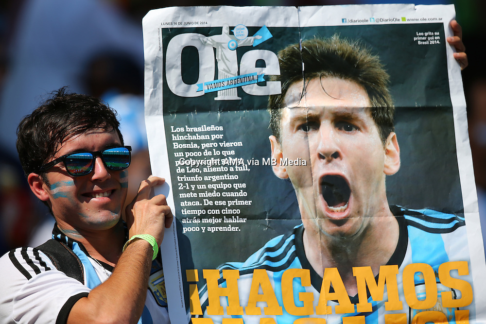 A fan of Argentina holds up a newspaper with a picture of Lionel Messi of Argentina