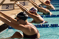 Female swimmers holding onto starting block preparing to swim backstroke