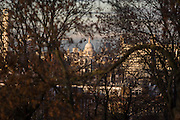 The dome of St Paul's Cathedral is seen through a gap in mature ash tree branches, from the London borough of Lambeth to the City of London, approximately 5 miles distant. The large crossing dome is composed of three layers: the first triple dome ever to be constructed. St Paul's Cathedral, London, is a Church of England cathedral and seat of the Bishop of London. Its dedication to Paul the Apostle dates back to the original church on this site, founded in AD 604. St Paul's sits at the top of Ludgate Hill, the highest point in the City of London, and is the mother church of the Diocese of London. The present church dating from the late 17th century was built to an English Baroque design of Sir Christopher Wren, as part of a major rebuilding program which took place in the city after the Great Fire of London, and was completed within his lifetime.