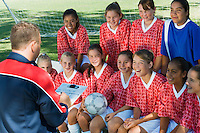 Coach Giving Pep Talk to Smiling Soccer Team