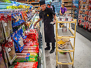 "27 MARCH 2015 - BANGKOK, THAILAND: A worker stocks shelves in Gourmet Market, a grocery store, in ""EmQuartier,"" a new mall in Bangkok. ""EmQuartier"" is across Sukhumvit Rd from Emporium. Both malls have the same corporate owner, The Mall Group, which reportedly spent 20Billion Thai Baht (about $600 million US) on the new mall and renovating the existing Emporium. EmQuartier and Emporium have about 450,000 square meters of retail, several hotels, numerous restaurants, movie theaters and the largest man made waterfall in Southeast Asia. EmQuartier celebrated its grand opening Friday, March 27.   PHOTO BY JACK KURTZ"
