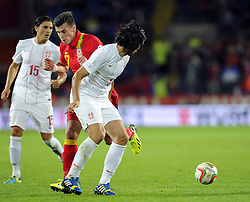 Gareth Bale of Wales (Real Madrid) is stopped by Milan Bisevac of Serbia (Lyon)- Photo mandatory by-line: Joe Meredith/JMP - Tel: Mobile: 07966 386802 10/09/2013 - SPORT - FOOTBALL - Cardiff City Stadium - Cardiff -  Wales V Serbia- World Cup Qualifier