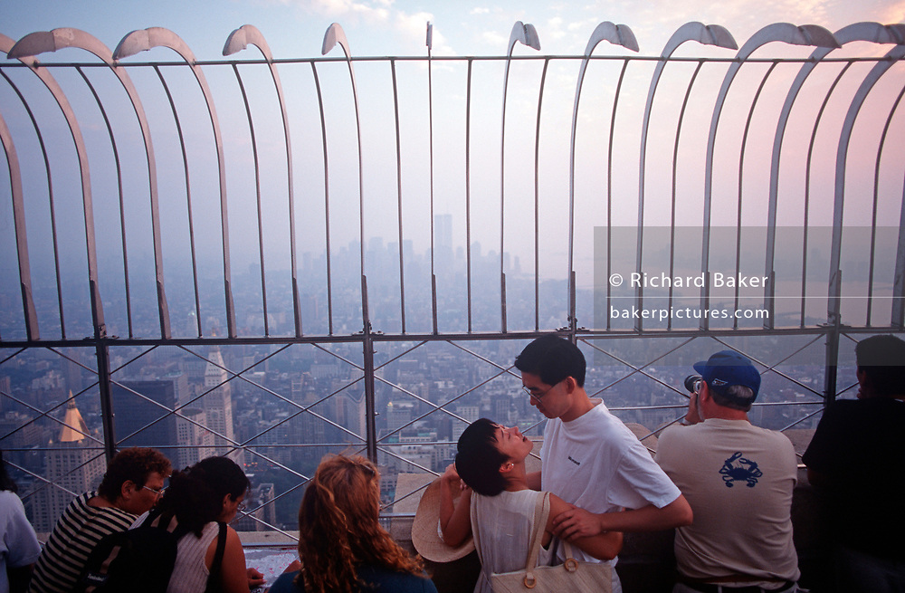 With the New York skyline shrouded in smog, a young Asian couple embrace on the open-air deck of the Empire State Building in Manhattan, on 31st July 1998, in New York, USA. (Photo by Richard Baker / In Pictures via Getty Images)