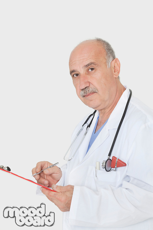Portrait of senior medical practitioner with clipboard over gray background