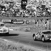 #14 Lindsay Saker Motors Porsche 904 (Drivers - Mike De Udy and Peter de Klerk) with #34 Team Lawson Volvo 122 S (Drivers - Frank Wingels and Jan Hettema) following through Clubhouse Corner, Kyalami 9-Hour Johannesburg South Africa 1965