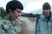 Two teenagers on the beach, one smoking a spliff, the other impatient for his turn, UK, 2000's