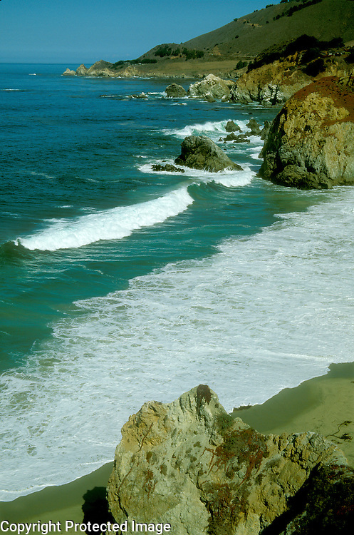 Breaking waves on rocky California coast and on beach in Big Sur region between Monterey and San Luis Obispo.