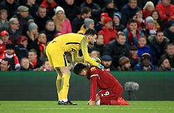 Tottenham Hotspur goalkeeper Hugo Lloris helps Liverpool's Roberto Firmino up during the Premier League match at Anfield, Liverpool.