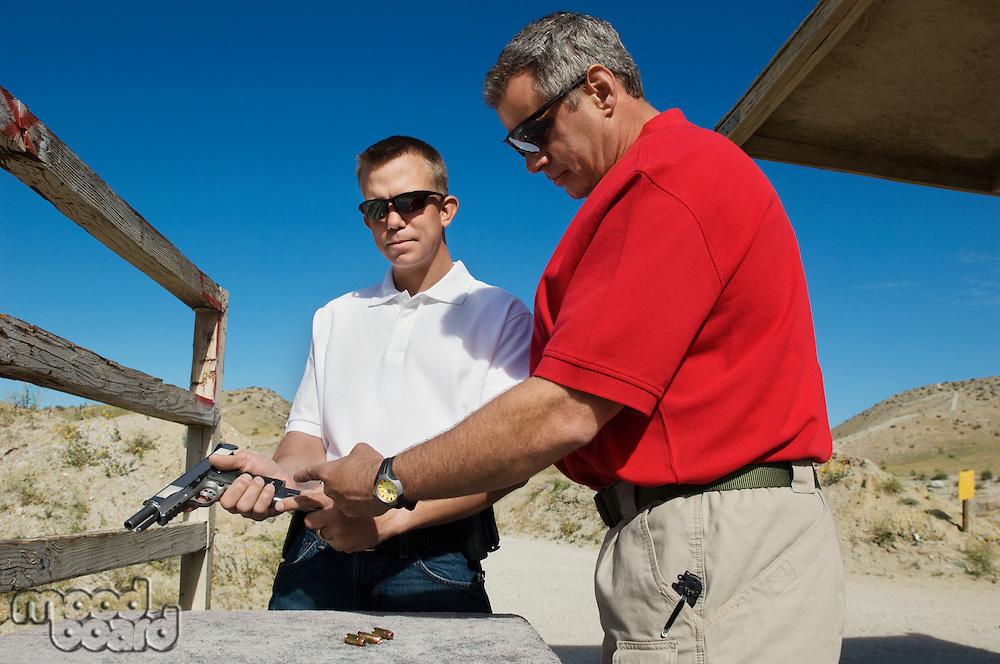 Instructor assisting man loading hand gun at firing range