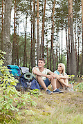 Full length of young hiking couple with backpacks relaxing in forest
