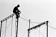 Silhouette of man on scaffolding pulling cables. Glastonbury 1994