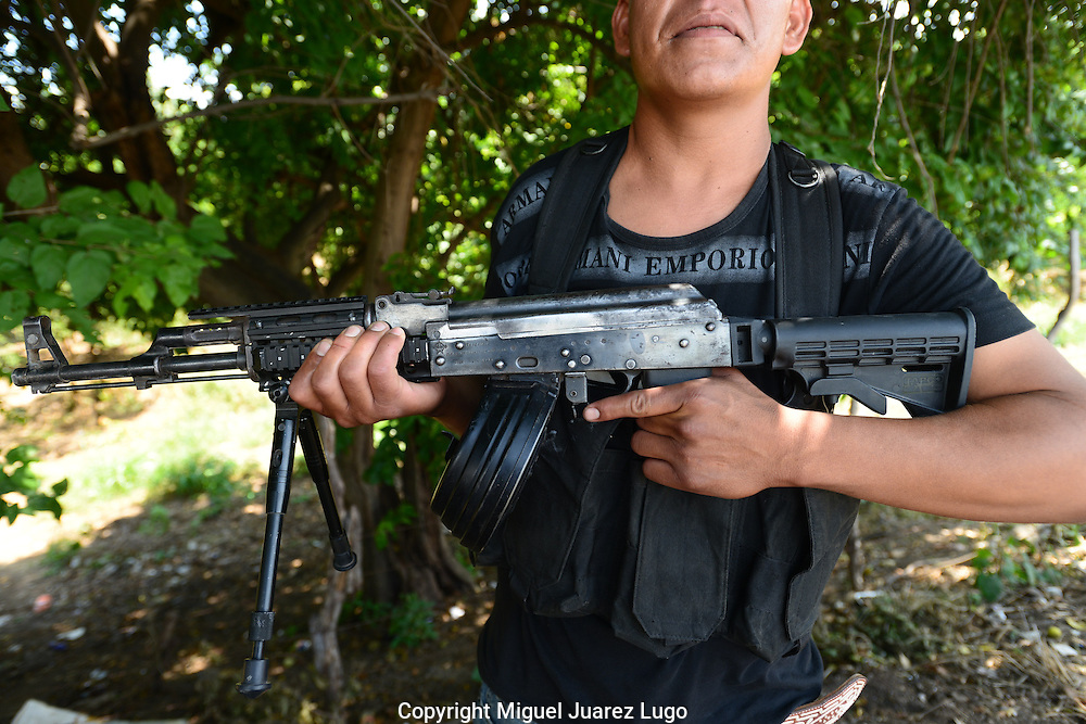 Member of a self-defense force shows an AK-47 with a high-storage ammunition cartridge that holds at least 500 rounds. The self-defense were at first armed only with shotguns and even slingshots but say they are increasingly seizing weapons, ammunition, bullet proof vests and other bounty as the Knights Templar drug gang flee towns.