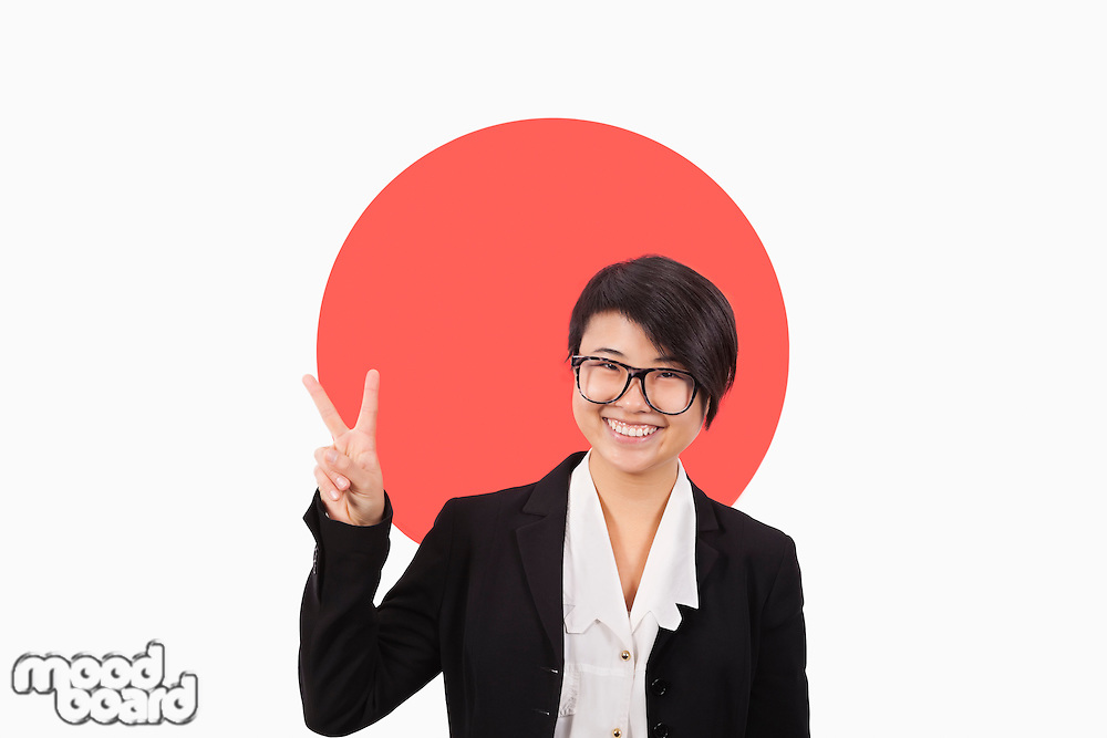 Portrait of young businesswoman gesturing peace sign over Japanese flag