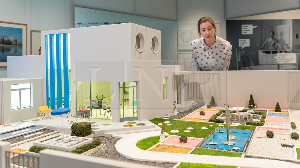 "© Licensed to London News Pictures. 06/11/2018. LONDON, UK. A staff member views ""Villa Arpel"", 1958/2002, by Jacques Lagrange and Jacques Tati. Preview of ""Home Futures"", at the Design Museum.  The exhibition, in partnership with IKEA Museum Almhult, asks are we living in the way that pioneering architects and designers once predicted, or has our idea of home proved resistant to real change?  More than 150 objects and experiences are on display 7 November to 24 March 2019.  Photo credit: Stephen Chung/LNP"