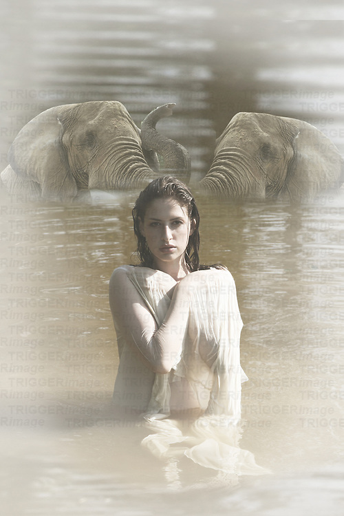 woman in water with elephants in the background