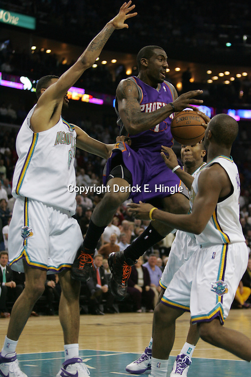 Amare Stoudemire #1 drives through the paint against New Orleans Hornets defenders Tyson Chandler #6, Chris Paul #3 (right) and David West #30 (back) on February 26, 2008 at the New Orleans Arena in New Orleans, Louisiana.