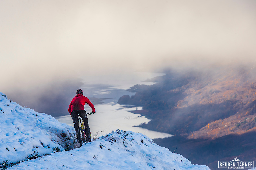Loch Leven forms the back drop as a rider drops down through the snow on stage three of the Kinlochleven Enduro,