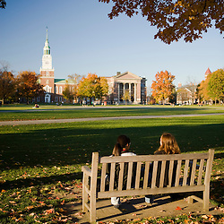 Two young women enjoy a conversation on the Dartmouth College Green in Hanover, New Hampshire.