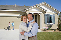 Portrait of mid-adult couple in front of new house, children (6-9) in background