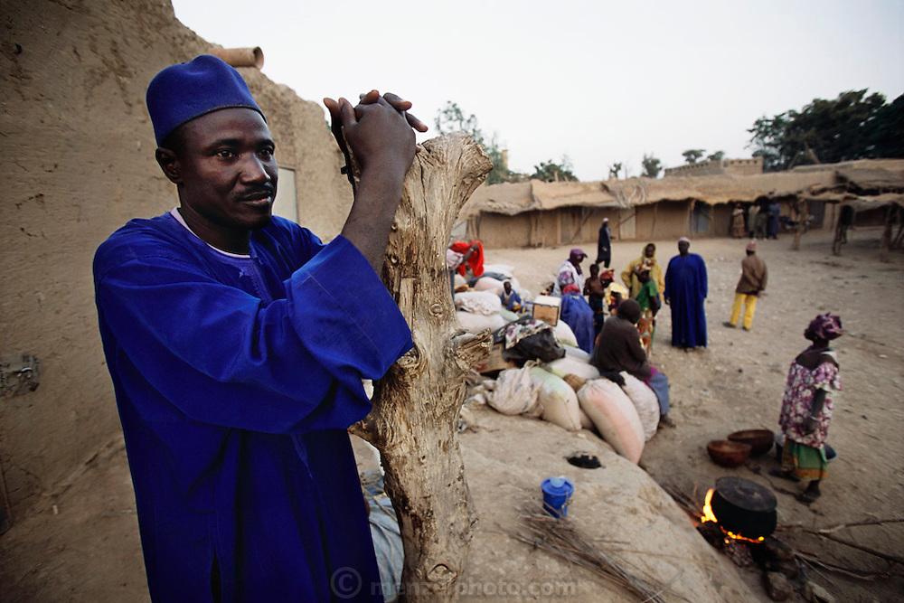 Soumana Natomo stands outside his small earthen grain shed, which sits above the weekly market grounds of Koukourou, his village located between the market town of Mopti and Djenne, Mali. He watches the merchants come by boat via the Niger River, in the early morning before the market begins, to set up stalls to sell their wares. Material World Project.