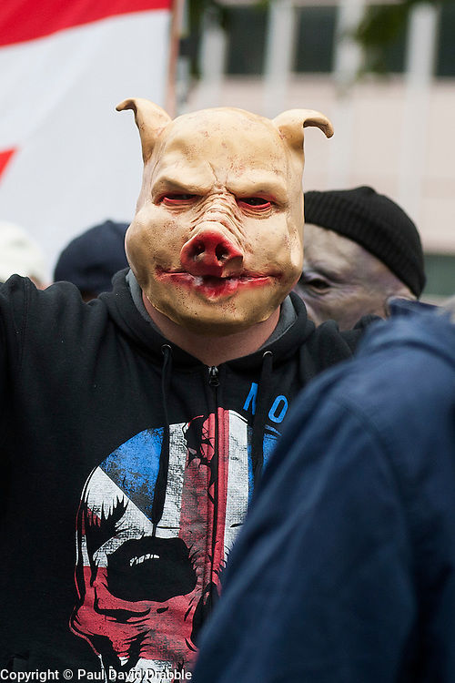 "Rotherham England<br /> 13 September 2014 <br /> EDL supporter wears a pig mask during a march from Rotherham Town Hall  to Rotherham Main Street Police station where they held a rally as part of the English Defence Leagues ""Justice for the Rotherham 1400"" March described by an EDL Facebook Page as ""a protest against the Pakistani Muslim grooming gangs"" on Saturday Afternoon <br /> <br /> <br /> Image © Paul David Drabble <br /> www.pauldaviddrabble.co.uk"