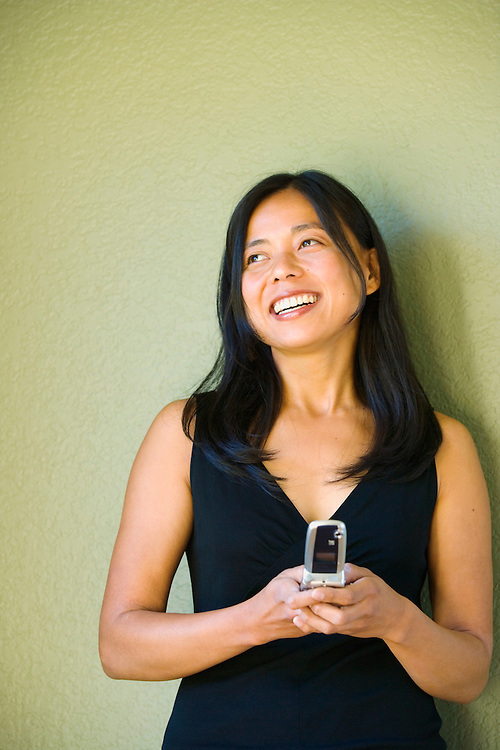 A smiling Japanese American woman in her late 20's standing in front of a green wall with her cell phone.20050910_MR_A.20050910_PR_A
