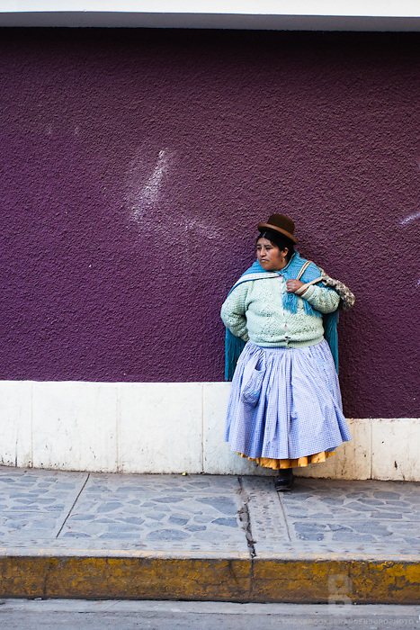 A women in a tradtional bowler hat and clothing set against a puple wall in Puno, Peru.