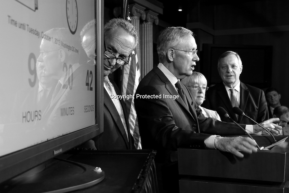 U.S. Senator Chuck Schumer (D-NY) (L-R), Senate Majority Leader Harry Reid (D-NV), Senator Patty Murray (D-WA) and Senator Dick Durbin (D-IL) stand with a clock counting down to a government shutdown at a news conference at the U.S. Capitol in Washington, September 30, 2013. The U.S. Congress, still in partisan deadlock on Monday over Republican efforts to halt President Barack Obama's healthcare reforms, was on the verge of shutting down most of the U.S. government starting on Tuesday morning.