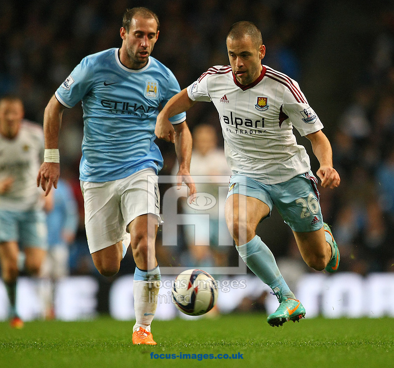 Picture by Paul Chesterton/Focus Images Ltd +44 7904 640267<br /> 08/01/2014<br /> Joe Cole of West Ham and Pablo Zabaleta of Man City in action during the Capital One Cup Semi Final 1st Leg match at the Etihad Stadium, Manchester.