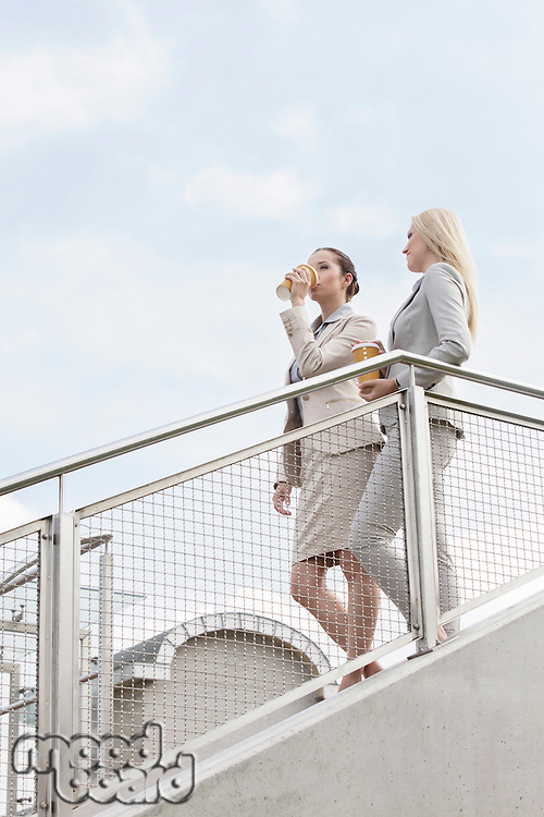 Young businesswomen with disposable coffee cups moving down stairs against sky