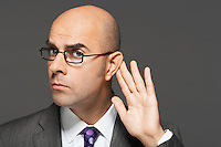 Balding man with hand behind ear listening closely