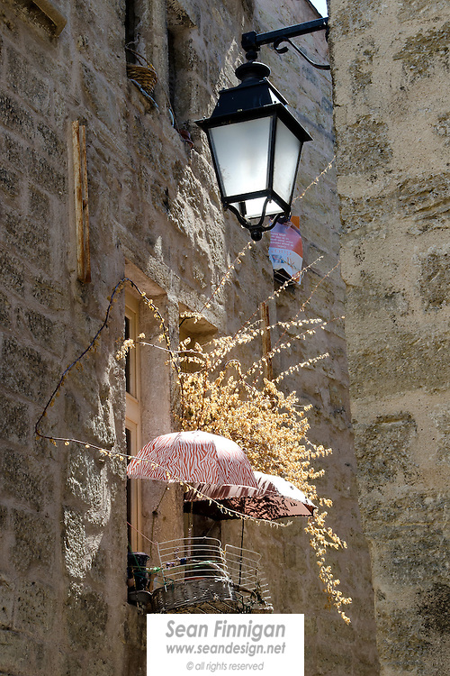 Umbrellas and dried flowers on display in the beautiful medieval town of Pézenas, a historic centre for art and culture in the Languedoc area of the south of France.