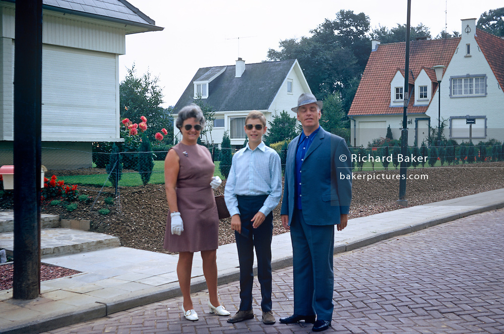 A middle-age mother and father with a teenage son pose for a photo outside their house in a Belgian suburb in the early 70s.