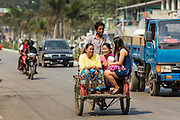 02 MARCH 2014 - MYAWADDY, KAYIN, MYANMAR (BURMA): A pedicab driver takes women into Myawaddy, Myanmar. Pedicabs are still used in much of Myanmar (Burma). Myawaddy is separated from the Thai border town of Mae Sot by the Moei River. Myawaddy is the most important trading point between Myanmar and Thailand.   PHOTO BY JACK KURTZ