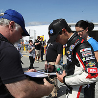 Clorox Chevrolet driver Kyle Larson signs autographs during a NASCAR Drive4COPD Nationwide Series practice session at Daytona International Speedway on Thursday, February 21, 2013 in Daytona Beach, Florida.  (AP Photo/Alex Menendez)