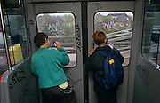Seen from behind, two young boys are busy writing their graffiti tags on windows on a London underground tube train, during an overland section of the capital's rail system near Ladbroke Grove in 1989.
