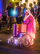 17 AUGUST 2015 - BANGKOK, THAILAND: A woman pushes a wheelchair at the scene of an explosion at Erawan Shrine. There are several large high end tourist hotels in the vicinity of the shrine and many hotel guests came out to watch the commotion. An explosion at Erawan Shrine, a popular tourist attraction and important religious shrine, in the heart of the Bangkok shopping district killed at least 19 people and injured more than 120 others, mostly foreign tourists, during the Monday evening rush hour. Twelve of the dead were killed at the scene. Thai police said an Improvised Explosive Device (IED) was detonated at 18.55. Police said the bomb was made of more than six pounds of TNT stuffed in a pipe and wrapped with white cloth. Its destructive radius was estimated at 100 meters. The Bangkok government announced that public schools would be closed Tuesday as a precaution.        PHOTO BY JACK KURTZ