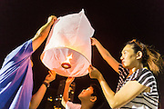 "17 NOVEMBER 2013 - BANGKOK, THAILAND: A family tries to launch a Yi Peng lantern on Loy Krathong near Wat Yannawa in Bangkok. The Yi Peng lanterns are Loy Krathong tradition in Chiang Mai but they are becoming more popular  in Bangkok and central Thailand. Loy Krathong (also written as Loi Krathong) is celebrated annually throughout Thailand and certain parts of Laos and Burma (in Shan State). The name could be translated ""Floating Crown"" or ""Floating Decoration"" and comes from the tradition of making buoyant decorations which are then floated on a river. Loi Krathong takes place on the evening of the full moon of the 12th month in the traditional and they do this all evening on the 12th month Thai lunar calendar. In the western calendar this usually falls in November. The candle venerates the Buddha with light, while the krathong's floating symbolizes letting go of all one's hatred, anger, and defilements       PHOTO BY JACK KURTZ"