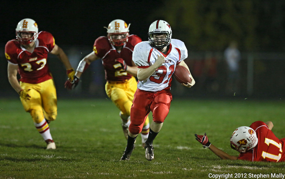 Western Dubuque's Dan Beard (31) avoids the defenders on a touchdown run during their first round playoff game at Thomas Park Field in Marion on Wednesday, October 24, 2012.