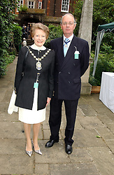 The Lord Mayor of Westminster COUNCILLOR CATHERINE LONGWORTH and her husband JOHN LONGWORTH at the annual House of Lords v House of Commons tug of war match in aid of  of  Macmillan Cancer Relief on 22nd June 2004.  A drinks reception was held in College Gardens followd by the tug of war on Victoria Tower Gardens, London.