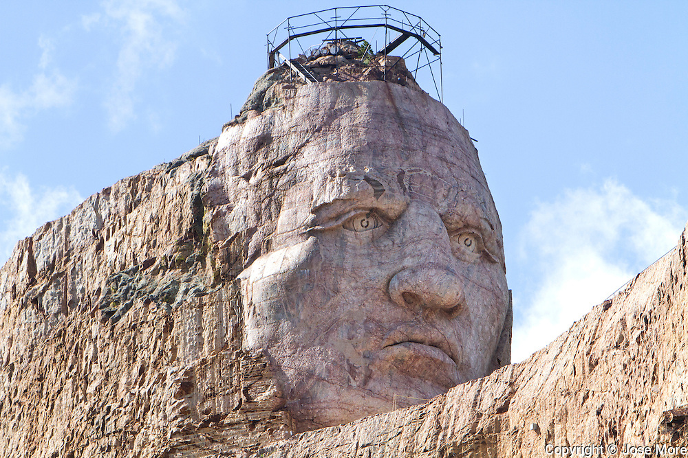 The Crazy Horse Memorial, a monument under construction on Thunderhead Mountain, a privately held land in the Black Hills, Custer County, South Dakota. It depicts Crazy Horse, an Oglala Lakota warrior, riding a horse and pointing into the distance. The memorial was commissioned by Henry Standing Bear, a Lakota elder, to be sculpted by Korczak Ziolkowski. Photography by Jose More