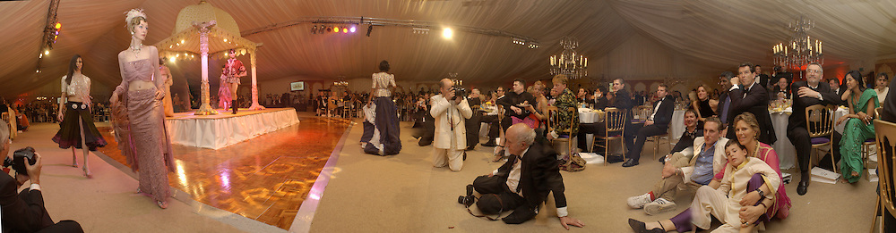 Watching the fashion show, Pierce Brosnan on right.  Indian Palace Ball in a tent in  St. James's Sq. gardens. 5 July 2002.  © Copyright Photograph by Dafydd Jones 66 Stockwell Park Rd. London SW9 0DA Tel 020 7733 0108 www.dafjones.com
