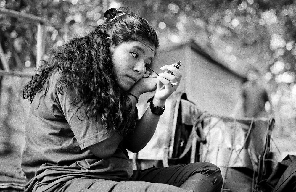 A female FARC fighter applies her make up in preperation for a New Year party being held in her camp in Caqueta.<br />