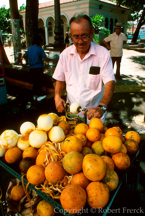 PUERTO RICO, SAN JUAN Old San Juan, street vendor peeling oranges